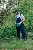 gardener in overalls and noise-canceling headphones pruning bushes with electric trimmer