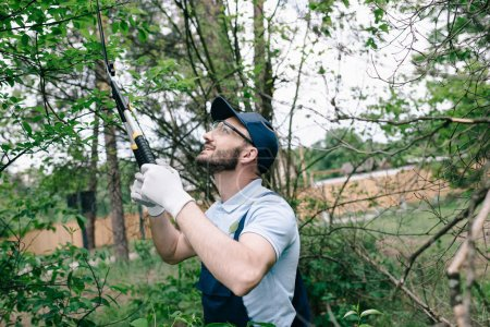 smiling gardener in protective glasses and cap cutting bushes with trimmer in park