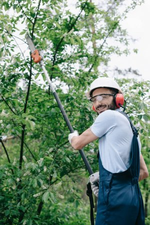 Photo for Smiling gardener in helmet trimming trees with telescopic pole saw and looking at camera - Royalty Free Image