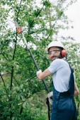 smiling gardener in helmet trimming trees with telescopic pole saw and looking at camera