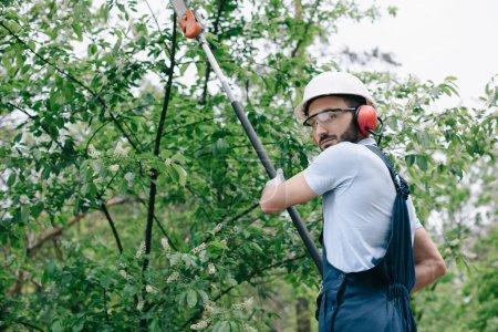Photo pour Jardinier sérieux dans les arbres de coupe de casque avec scie à perche télescopique et regardant la caméra - image libre de droit