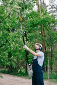 gardener in overalls, helmet and hearing protectors trimming trees with telescopic pole saw in garden