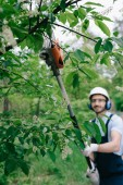selective focus of smiling gardener in helmet and hearing protectors trimming trees with telescopic pole saw and looking at camera