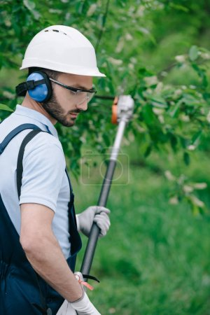 Photo for Selective focus of thoughtful gardener in helmet and hearing protectors trimming trees with telescopic pole saw in garden - Royalty Free Image