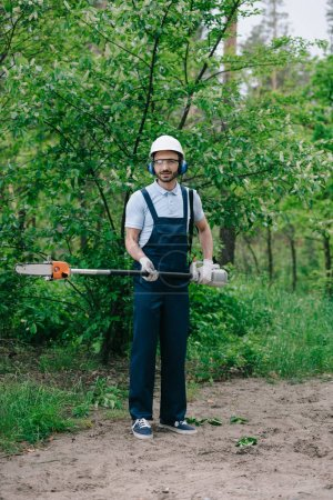 Photo for Handsome gardener in overalls, helmet and earmuffs holding telescopic pole saw and looking at camera - Royalty Free Image