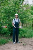 handsome gardener in overalls, helmet and earmuffs holding telescopic pole saw and looking at camera