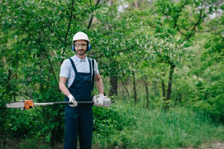 Photo for Cheerful gardener in overalls, helmet and hearing protectors holding telescopic pole saw and smiling at camera - Royalty Free Image