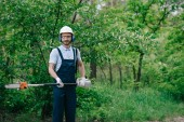 cheerful gardener in overalls, helmet and hearing protectors holding telescopic pole saw and smiling at camera
