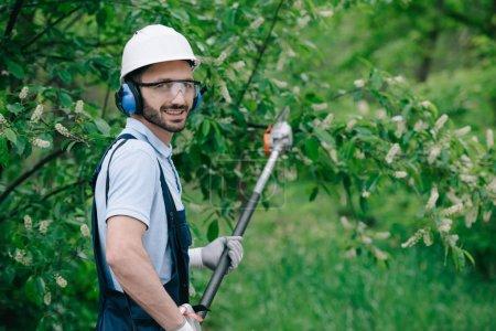 Foto de Hermoso jardinero en casco, gafas protectoras y auriculares con cancelación de ruido que sostienen sierra de poste telescópica y sonriendo a la cámara - Imagen libre de derechos