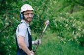 """Постер, картина, фотообои """"красивый садовник в шлеме, защитных очках и шумоподавляющих наушниках, держащих телескопическую пилу полюса и улыбающегося на камеру"""""""