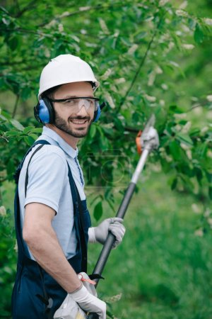 Photo for Cheerful gardener in helmet, protective glasses and noise-canceling headphones holding telescopic pole saw and smiling at camera - Royalty Free Image