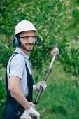 """Постер, картина, фотообои """"веселый садовник в шлеме, защитных очках и шумоподавляющих наушниках, держащих телескопическую пилу полюса и улыбающуюся на камеру"""""""