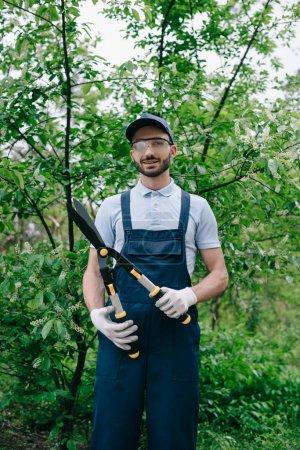 Photo pour Beau jardinier en salopette, chapeau et verres protecteurs tenant le tailleur et souriant à l'appareil-photo - image libre de droit