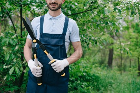 Photo for Partial view of smiling gardener in overalls holding trimmer in garden - Royalty Free Image