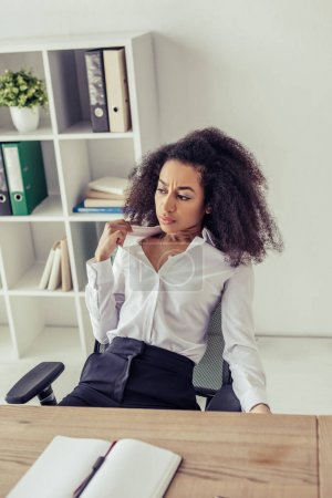 Photo for Attractive african american woman suffering from summer heat while sitting at workplace in office - Royalty Free Image