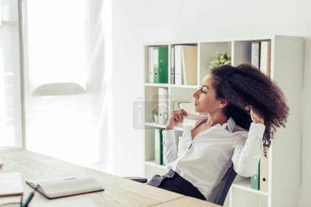 Photo pour Pretty african american businesswoman looking away while sitting at workplace and suffering from heat in office - image libre de droit