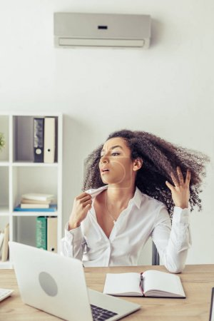 Foto de Exhausted african american businesswoman suffering from heat while sitting at workplace near laptop and notebook - Imagen libre de derechos