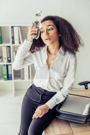 Photo for Exhausted african american businesswoman holding plastic bottle with water near head while suffering from heat in office - Royalty Free Image