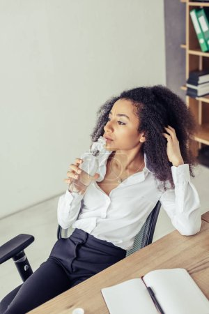 Photo for Pensive african american businesswoman drinking water and looking away while suffering from heat in office - Royalty Free Image