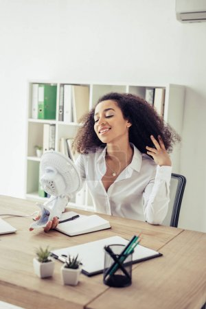 Photo pour Femme d'affaires afro-américaine gaie retenant l'amusement électrique tout en souffrant de la chaleur dans le bureau - image libre de droit