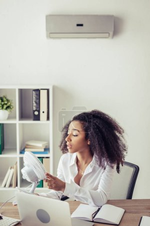 Foto de African american businesswoman holding blowing electric fan while sitting at workplace under air conditioner - Imagen libre de derechos