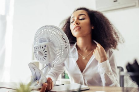 Photo pour Selective focus of attractive african american businesswoman holding electric fan while sitting at workplace - image libre de droit