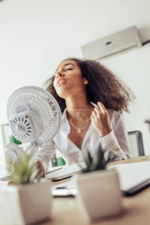 Photo pour Selective focus of african american businesswoman holding electric fan while suffering from heat in office - image libre de droit