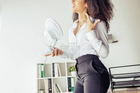 Photo for Partial view of african american businesswoman holding desk fan while suffering from heat in office - Royalty Free Image