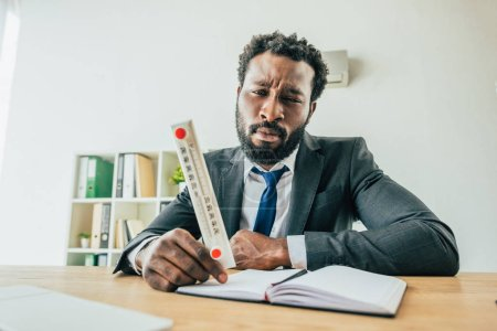 Photo for Unhappy african american businessman holding thermometer showing high temperature while sitting at workplace in office - Royalty Free Image