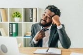 """Постер, картина, фотообои """"dissatisfied african american businessman touching tie while sitting at workplace and suffering from heat in office"""""""