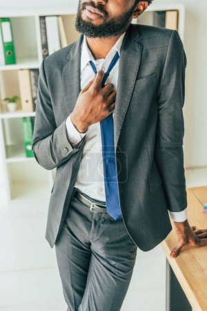 Photo for Cropped view of african american businessman standing at workplace and touching tie while suffering from heat in office - Royalty Free Image