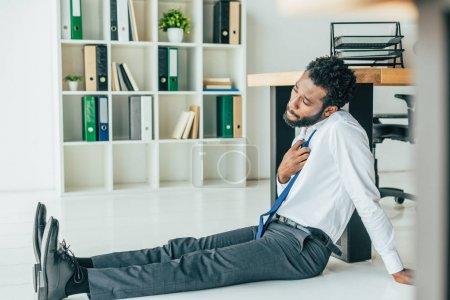 Foto de Selective focus of young african american businessman sitting on floor while suffering from summer heat - Imagen libre de derechos