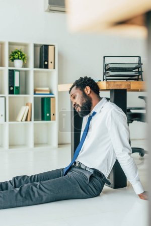 Photo for Selective focus of exhausted african american businessman sitting on floor while suffering from heat in office - Royalty Free Image