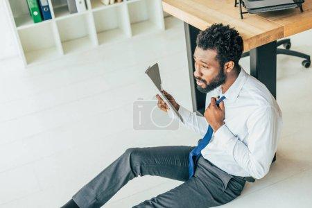 Foto de Joven empresario afroamericano sentado en el suelo y agitando con la carpeta mientras sufre de calor en la oficina - Imagen libre de derechos