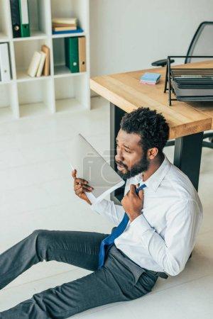 Foto de Agotado hombre de negocios afroamericano sentado en el suelo cerca del lugar de trabajo y agitando con la carpeta mientras sufre de calor - Imagen libre de derechos