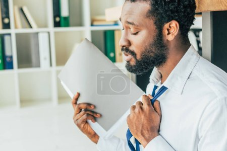 Photo for Dissatisfied african american businessman touching tie and waving with folder while suffering from heat in office - Royalty Free Image