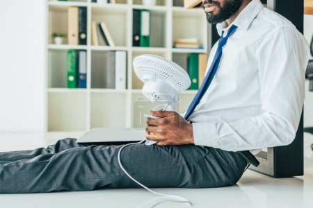 Photo pour Cropped view of african american businessman sitting on floor and holding electric fan while suffering from heat in office - image libre de droit