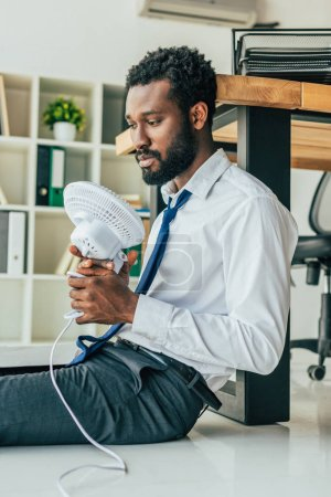Photo pour Homme d'affaires américain africain pensive retenant le ventilateur électrique tout en s'asseyant sur l'étage et souffrant de la chaleur d'été - image libre de droit