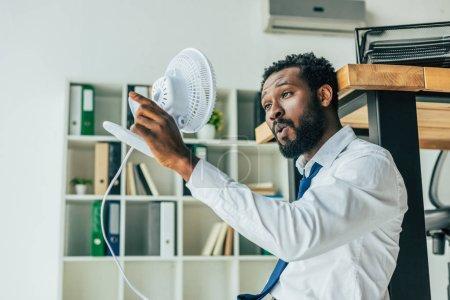 Photo pour Jeune homme d'affaires afro-américain tenant souffler ventilateur électrique tout en étant assis sur le sol et souffrant de chaleur dans le bureau - image libre de droit