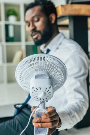 Photo pour Foyer sélectif de l'homme d'affaires américain africain s'asseyant sur l'étage et retenant le ventilateur électrique - image libre de droit