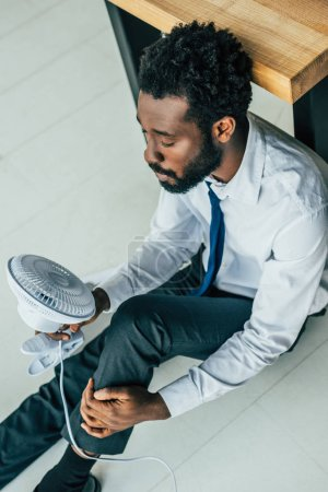 Photo for Overhead view of african american businessman sitting on floor with electric fan and suffering from heat - Royalty Free Image