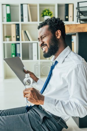 Photo pour Homme d'affaires américain africain épuisé agitant avec le dossier et retenant la bouteille d'eau tout en s'asseyant sur l'étage et souffrant de la chaleur - image libre de droit