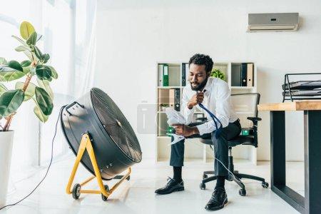 Photo pour Ventilateur africain américain de fixation de bureau tout en s'asseyant devant le ventilateur électrique dans le bureau - image libre de droit