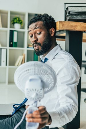 Photo pour Handsome african american businessman holding blowing electric fan while sitting on floor in office - image libre de droit