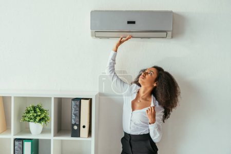 pretty african american businesswoman touching air conditioner while suffering from heat in office