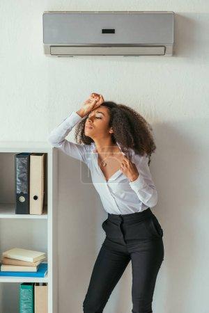 Photo pour Femme d'affaires afro-américaine épuisée retenant la main sur la tête tout en restant sous le climatiseur dans le bureau - image libre de droit