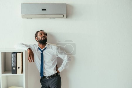 Photo for Young african american businessman standing under air conditioner and holding hand on hip - Royalty Free Image
