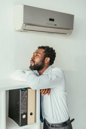 Photo for Pensive african american businessman standing under air conditioner and looking away in office - Royalty Free Image