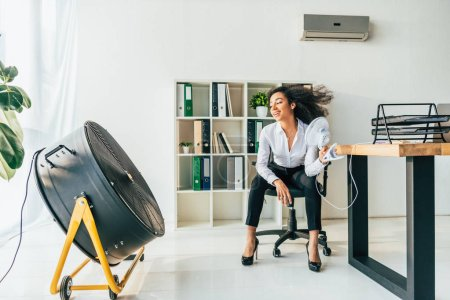 Photo for Smiling african american businesswoman sitting on office chair in front of electric ventilator in office - Royalty Free Image