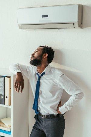 Photo pour Homme d'affaires américain africain réfléchi restant sous le climatiseur et retenant la main sur la hanche dans le bureau - image libre de droit